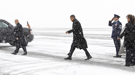 U.S. President Obama makes his way from Air Force One to his motorcade upon his arrival during a snowstorm in Manchester