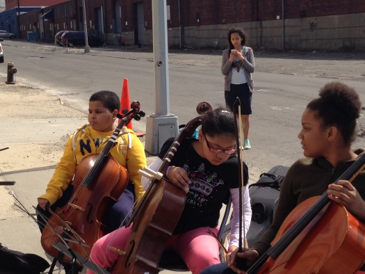 Local children playing cello join the demonstration